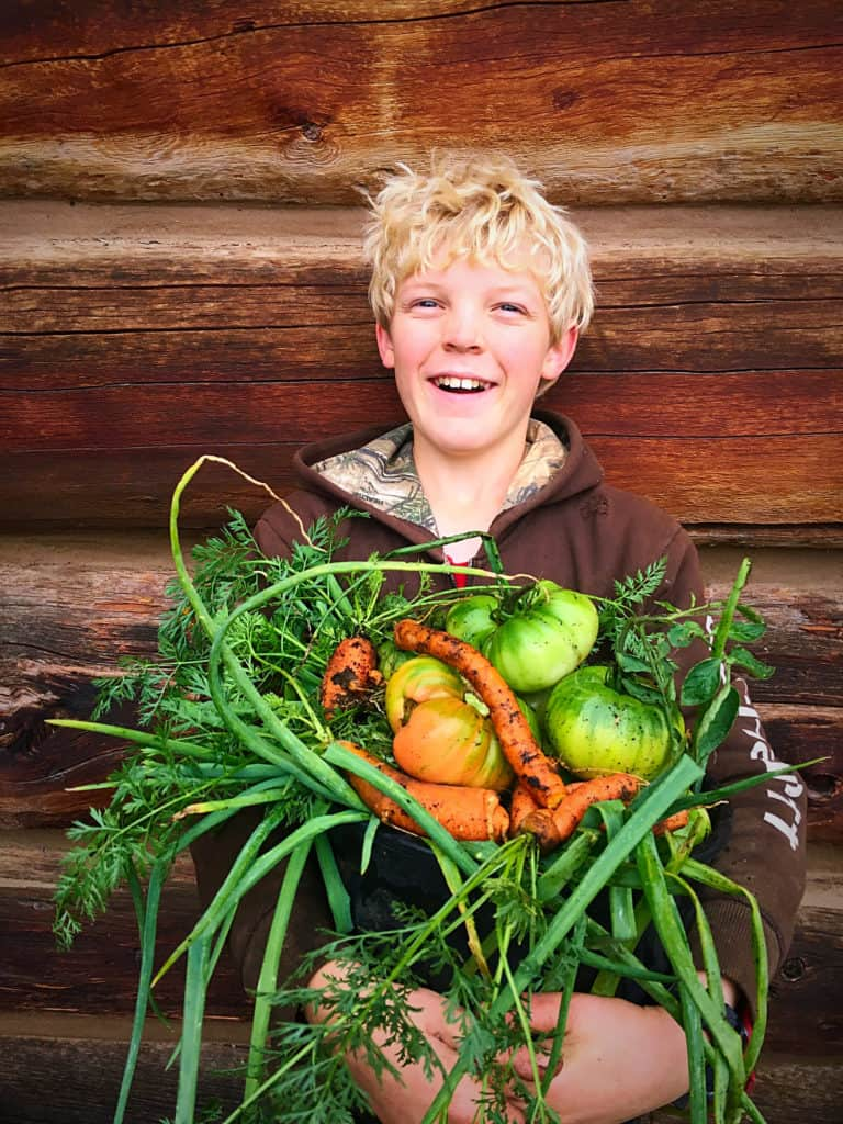 Young boy holding a basket filled with fresh produce.