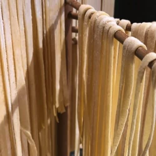 Homemade egg noodles drying on a noodle rack.