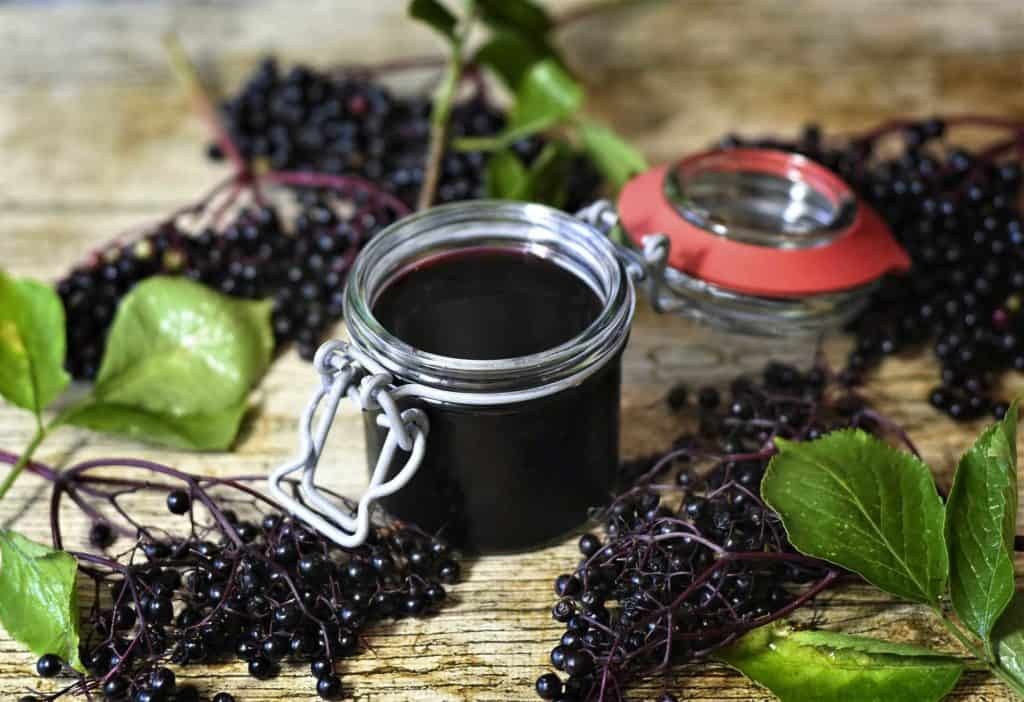 A jar of elderberry syrup with fresh picked elderberries around it.