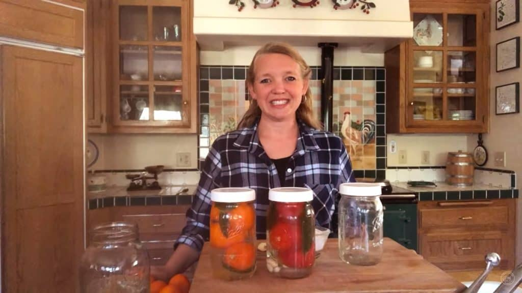 Woman standing behind three glass mason jars filled with fermented tomatoes.