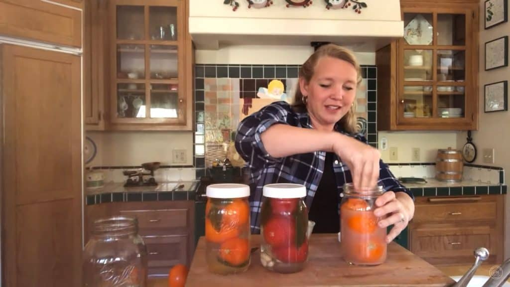 Woman stuffing tomatoes into a glass mason jar.