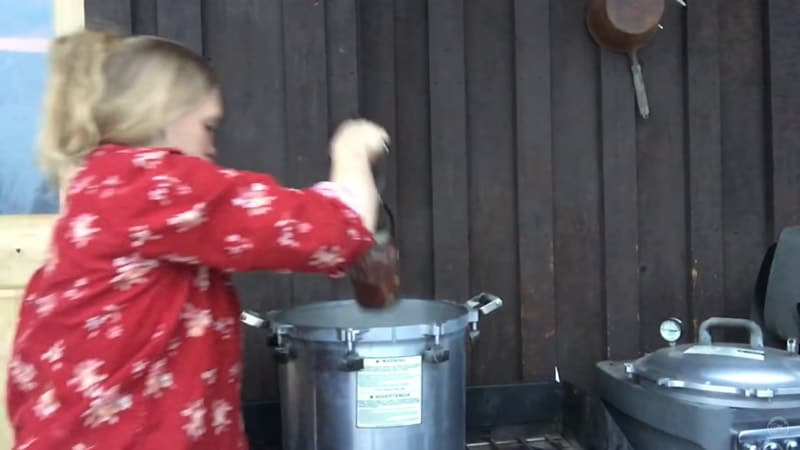 Woman lowering a jar of venison into a pressure canner.
