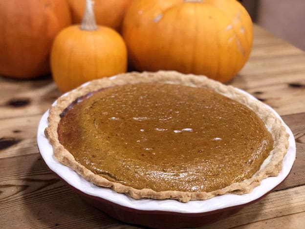 A pumpkin pie sitting on a table with fresh pumpkins in the background.