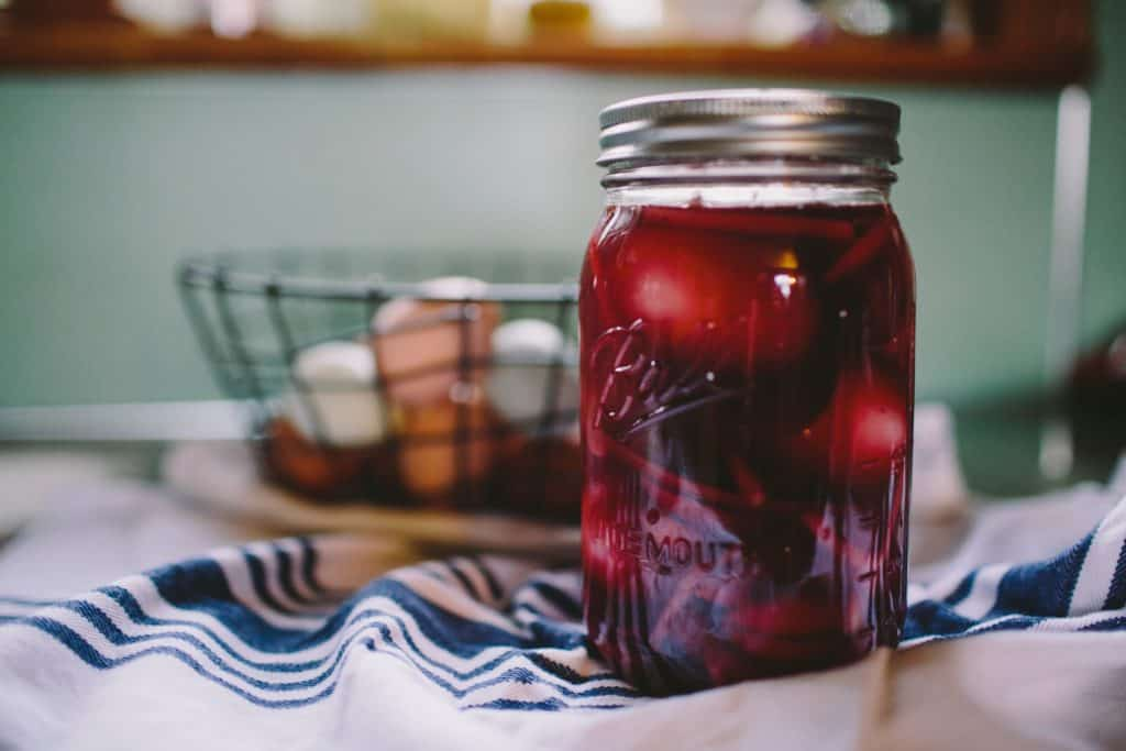 Jar of pickled eggs with a basket of fresh eggs in the background. Photo by Natalie Rhea Riggs on Unsplash
