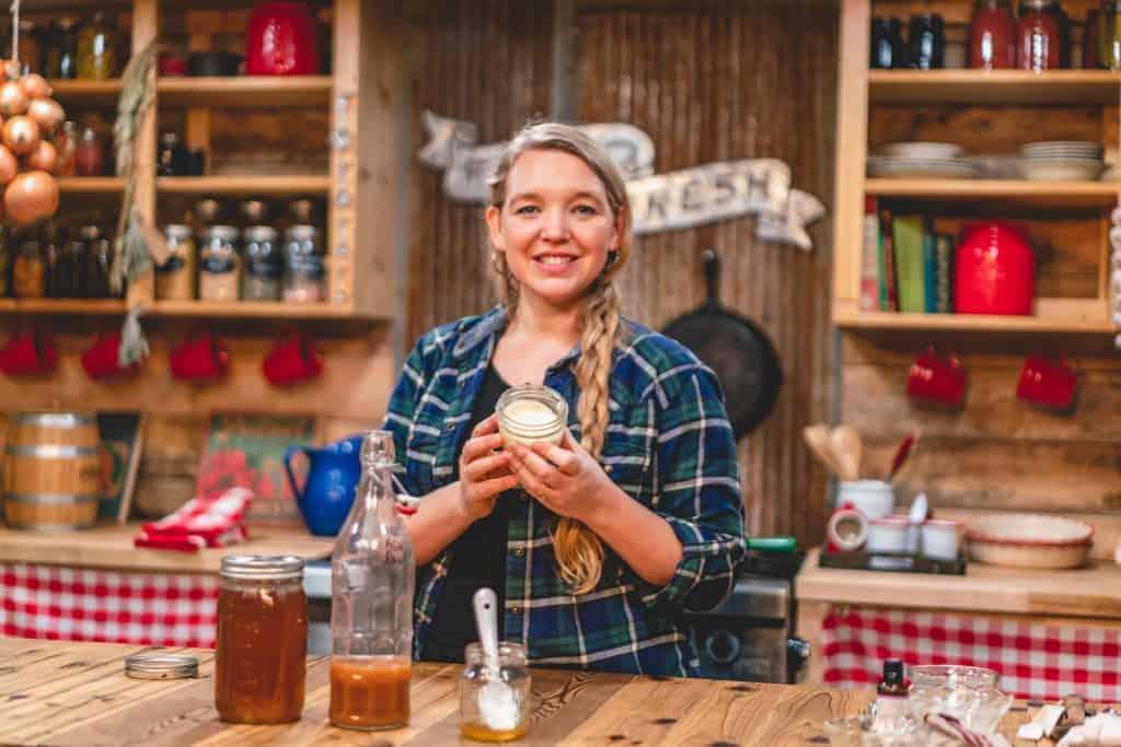 Woman holding a jar of garlic salve in her kitchen.