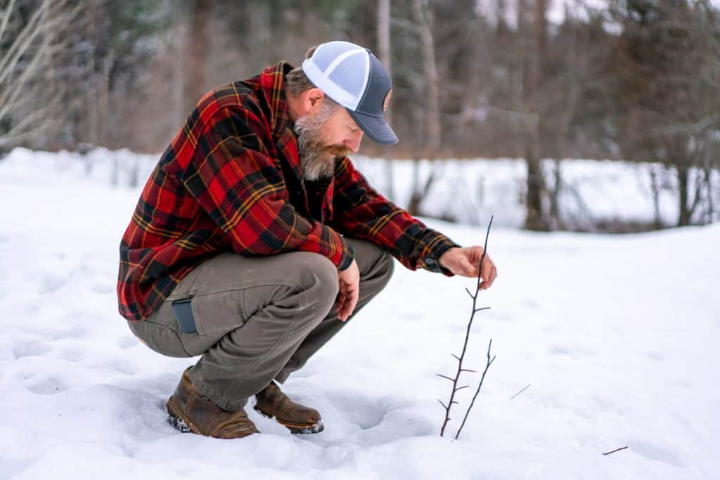 Man squatting next to a small tree outside in the snow.