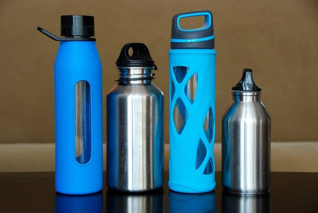 Four reusable water bottles on a counter.