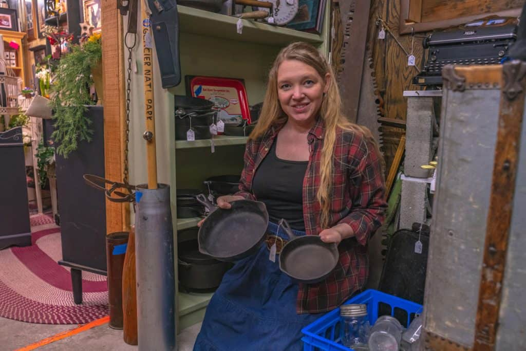 A woman holding two small cast iron pans in an antique store.