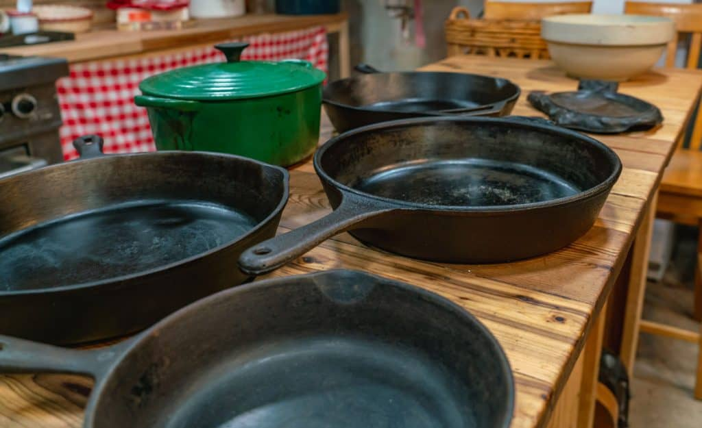Side view of cast iron pots and pans sitting on a wooden table.