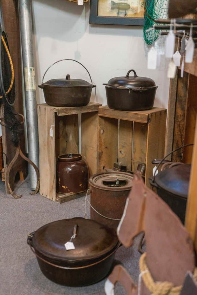 Cast iron pots and pans displayed at an antique store.