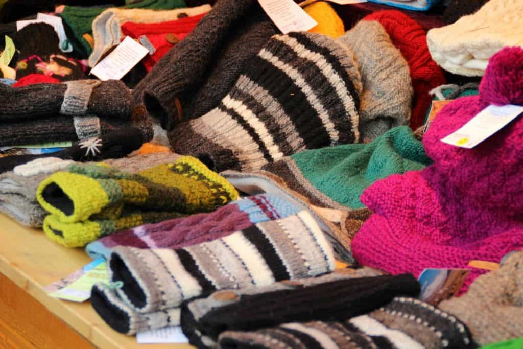 Multiple wool hats and gloves laid out on a table.