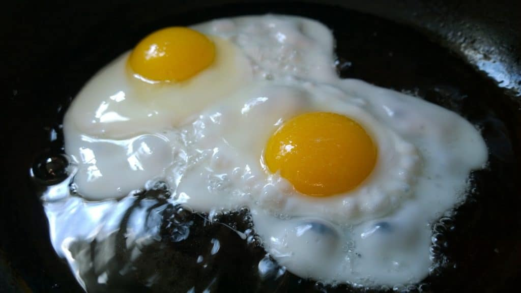 Two fried eggs cooking in a cast iron pan.