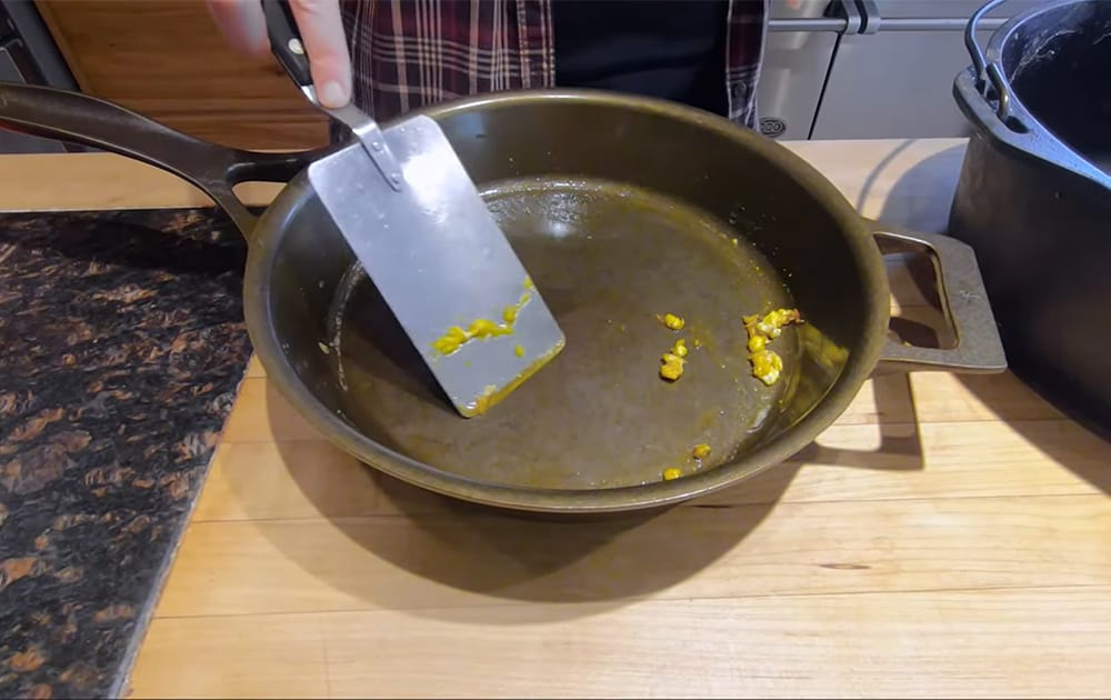 A cast iron pan being scraped with a metal spatula to get remaining egg residue unstuck.