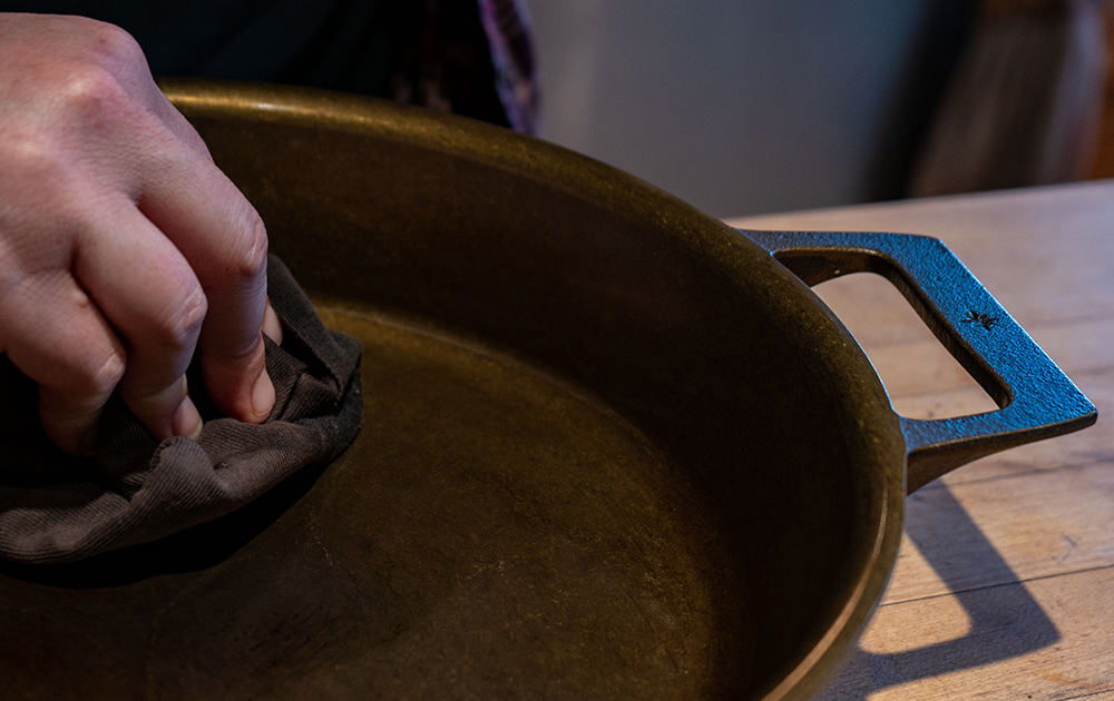 Up close image of a hand seasoning a cast iron skillet.