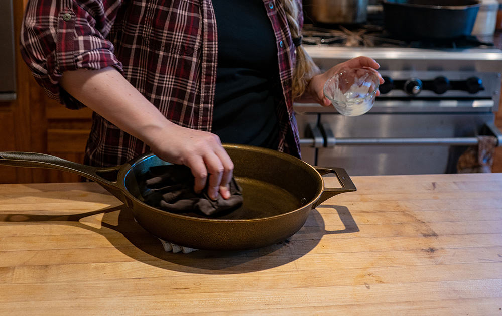 A woman seasoning a cast iron skillet with coconut oil.