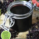 """Picture of elderberry syrup in a jar with elderberries on branches around it. Text overlay says, """"Build Your Immune System""""."""