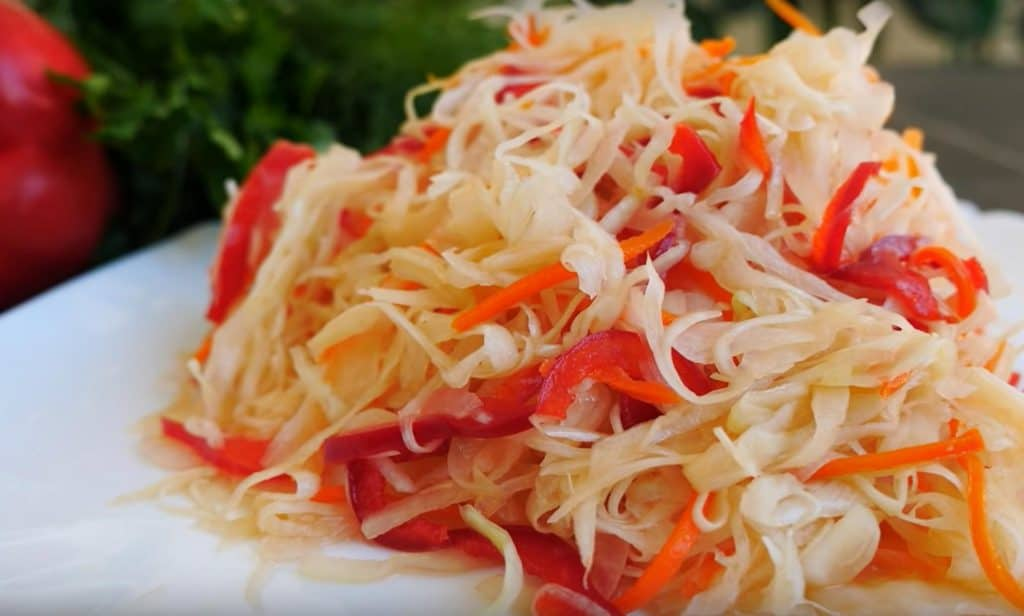 A white plate with a pile of sauerkraut with peppers and carrots mixed into it.
