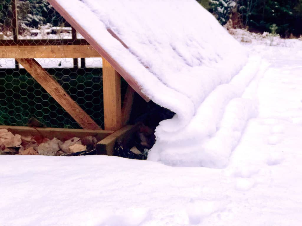 A-frame chicken tractor with snow sliding off the roof.