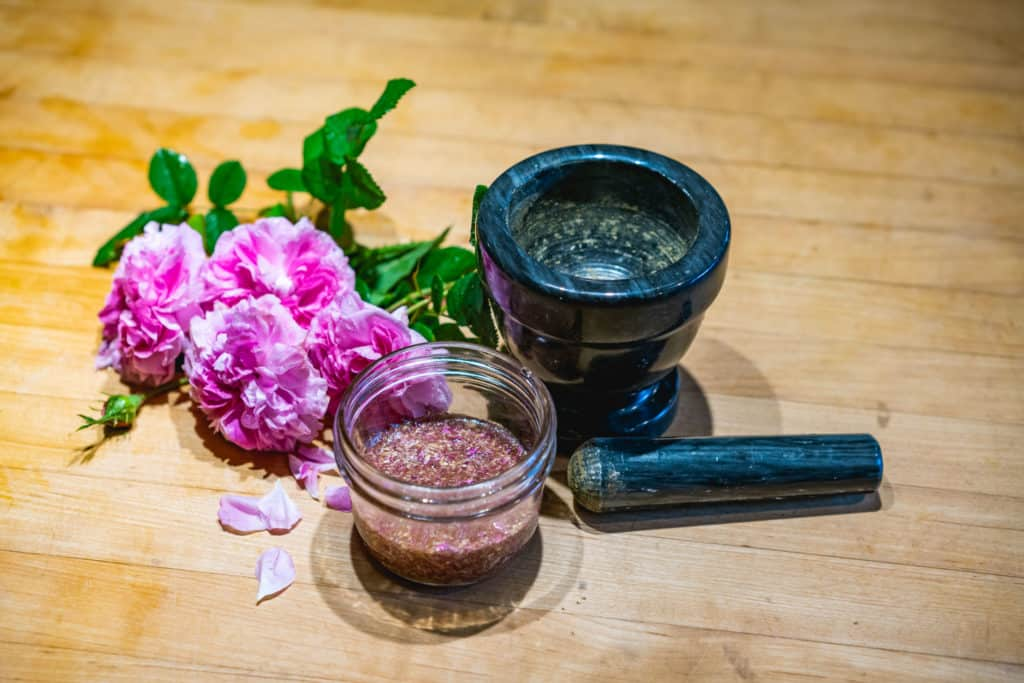Vertical view of rose face wash in a mason jar next to fresh roses and a mortar and pestle.
