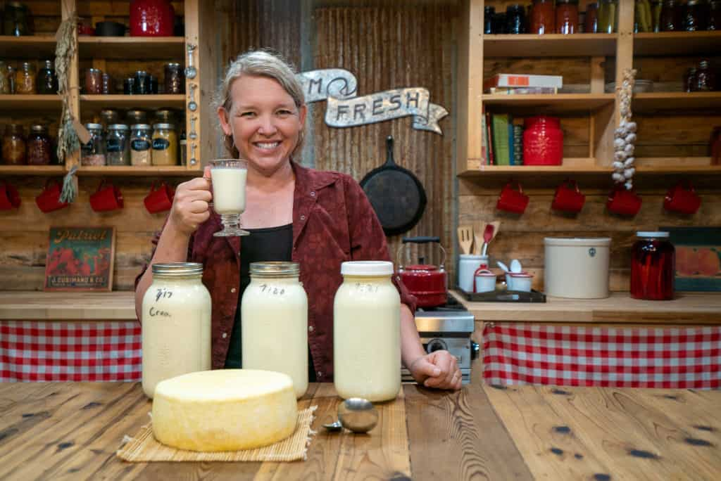 A woman holding up a glass of milk with three jars of milk in front of her and a large cheese wheel on the counter.