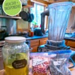 "Pinterest pin of a jar of greens powder with smoothie ingredients on the counter next to a blender. Text overlay says, ""Homemade Super Greens Powder."""