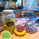 """Pinterest pin of a jar of greens powder with smoothie ingredients on the counter next to a blender. Text overlay says, """"Homemade Super Greens Powder."""""""