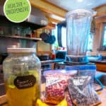 "Pinterest pin of a jar of greens powder with smoothie ingredients on the counter next to a blender. Text overlay says, ""Make Your Own Greens Powder."""