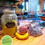 """Pinterest pin of a jar of greens powder with smoothie ingredients on the counter next to a blender. Text overlay says, """"Make Your Own Greens Powder."""""""
