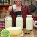"A Pinterest pin with an image of a woman holding up a glass of milk and three jars of milk plus a large cheese wheel on a counter in front of her. Text overlay says, ""The Anatomy of Raw Milk + What To Do With It""."