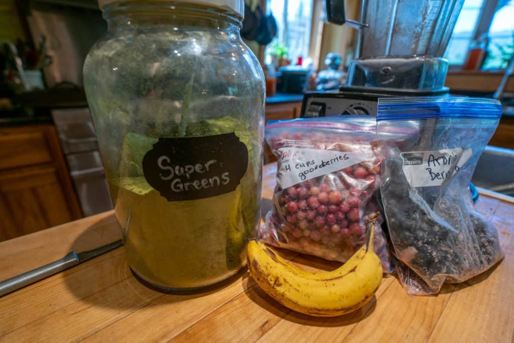 Super Greens Powder in a gallon jar with label next to frozen fruit and other smoothie ingredients.