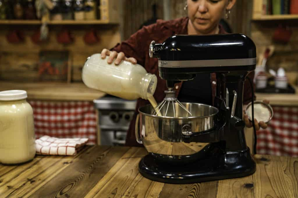 A woman pouring cream into a stand mixer.