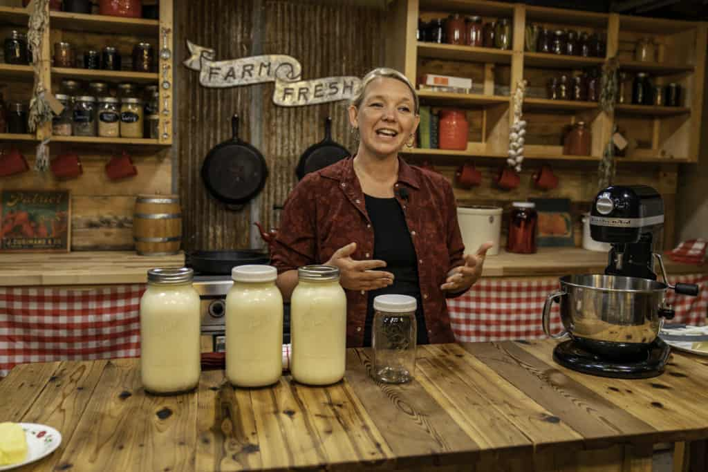A woman standing behind 3 jars of cream sitting on the kitchen counter.
