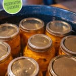 Photo of mason jars of food in a water bath canner. Pinterest pin of what to preserve each month of the year.