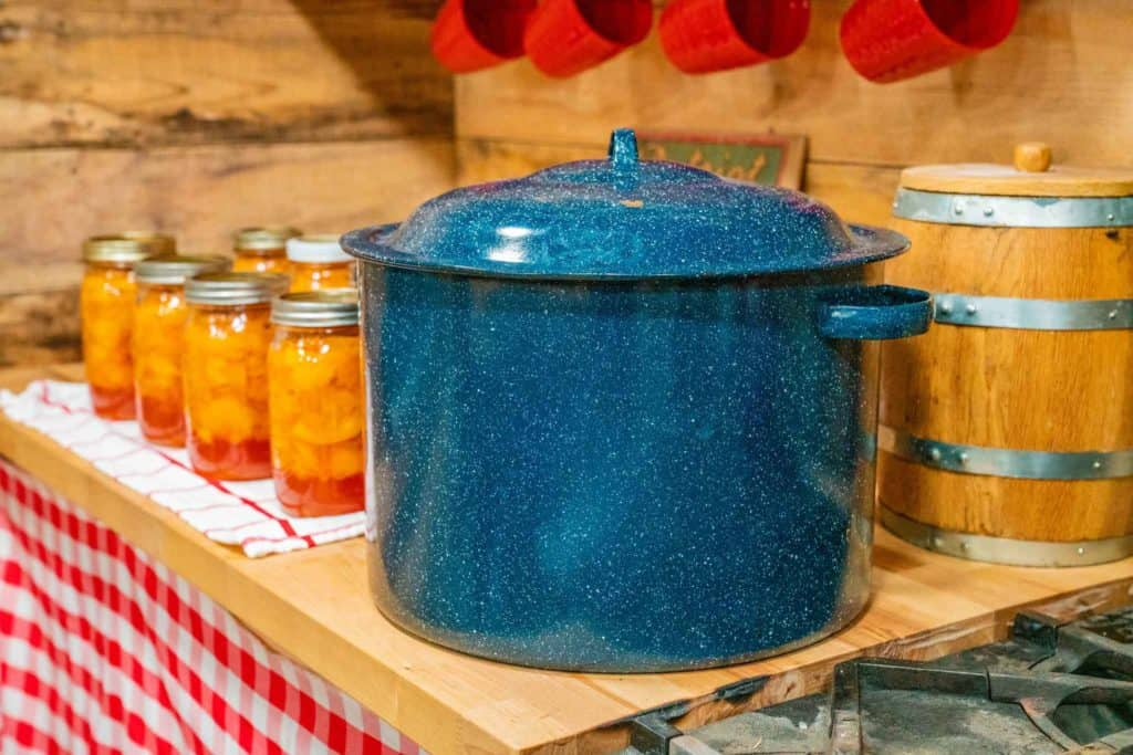 A blue water bath canner next to multiple jars of canned peaches sitting on a butcher block counter top.