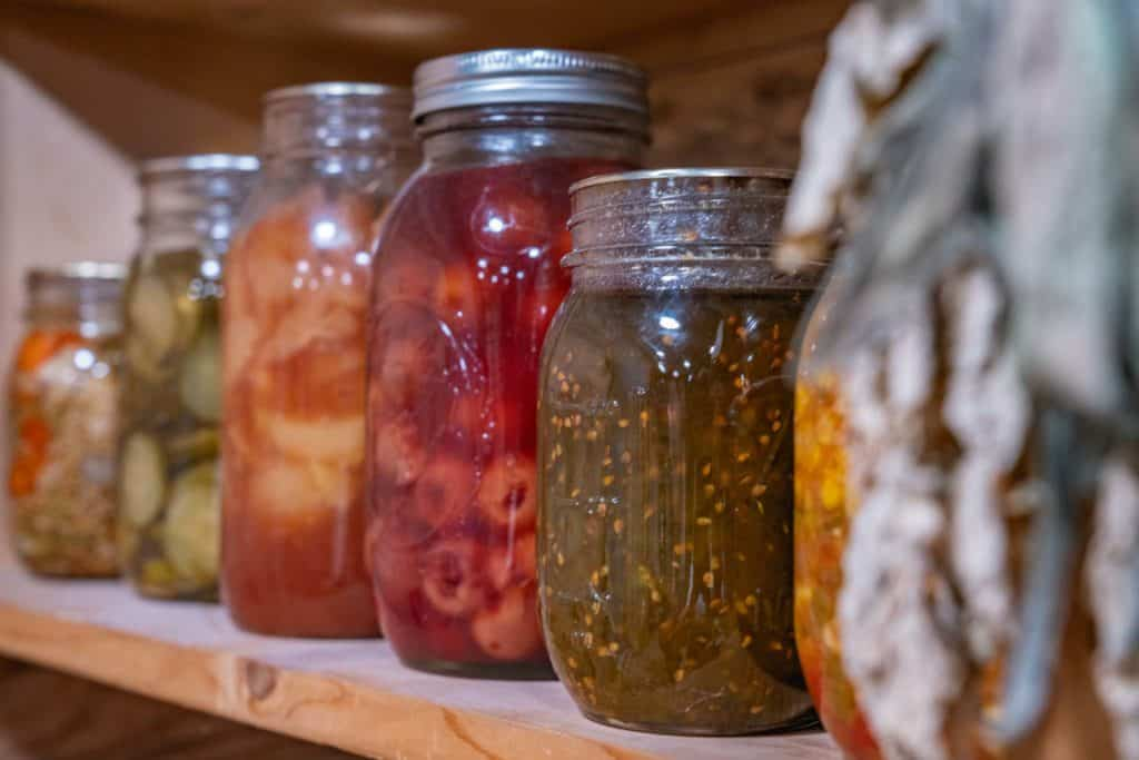Jars of food lined up on a pantry shelf.