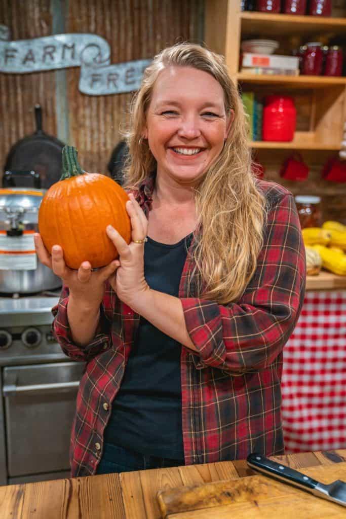 A woman holding up a pie pumpkin.