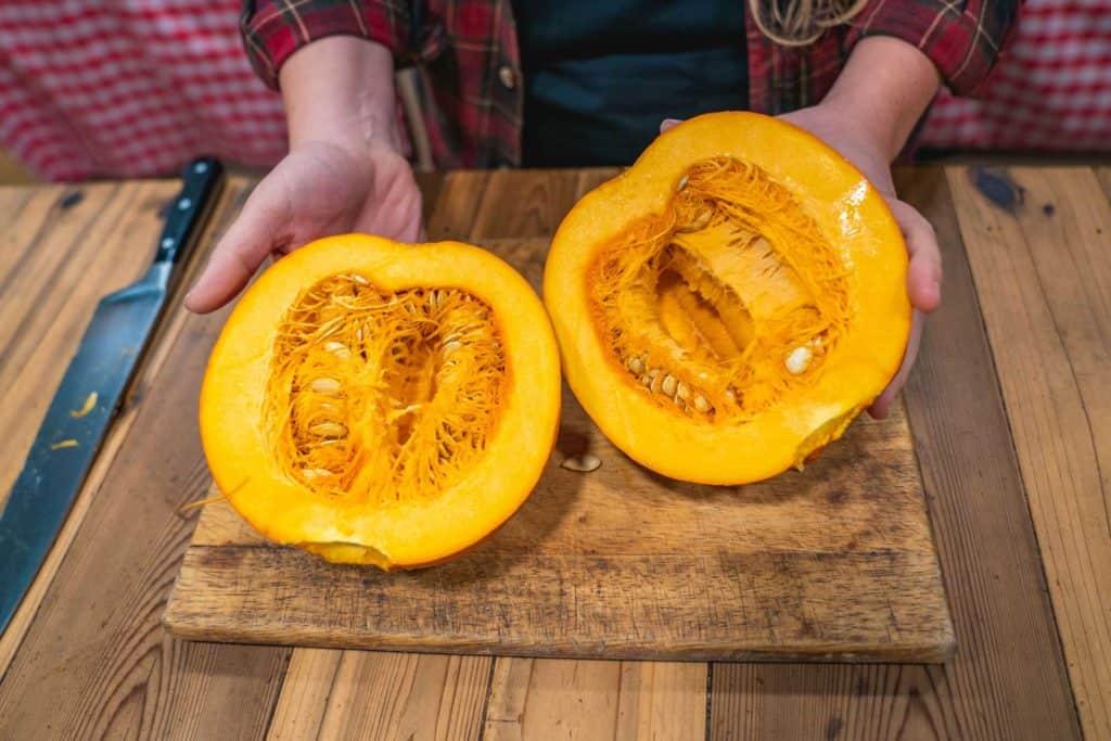 A pumpkin cut in half on a counter.