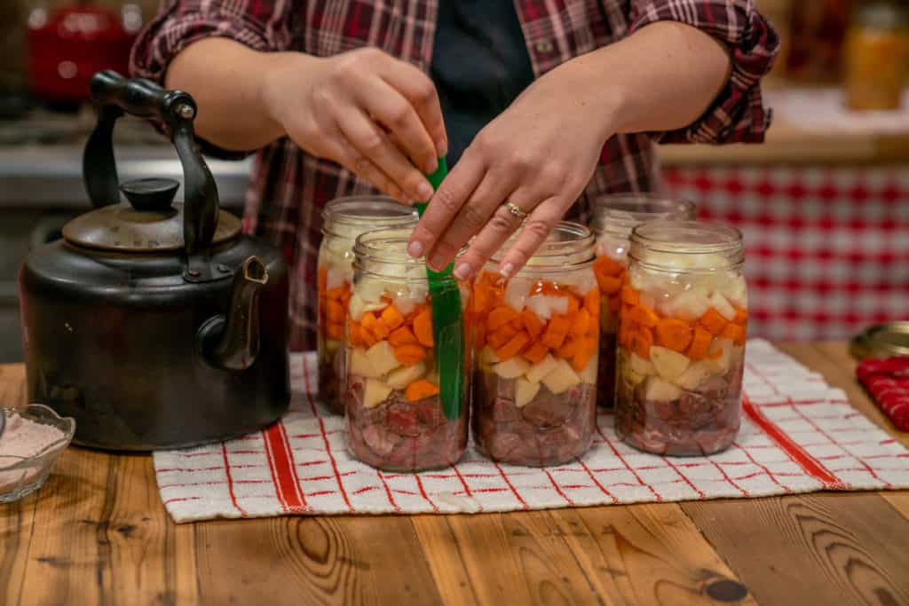 Six jars of raw packed canned stew with a canning tool sliding into one jar to remove air bubbles.