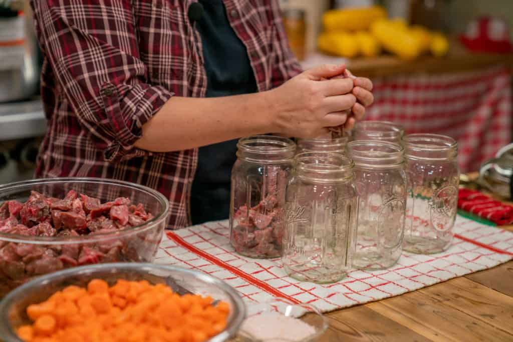 A woman placing raw cubed meat into canning jars.