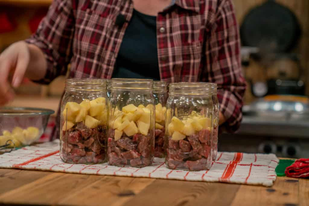 A woman adding raw, peeled potatoes to jars for homemade canned stew.