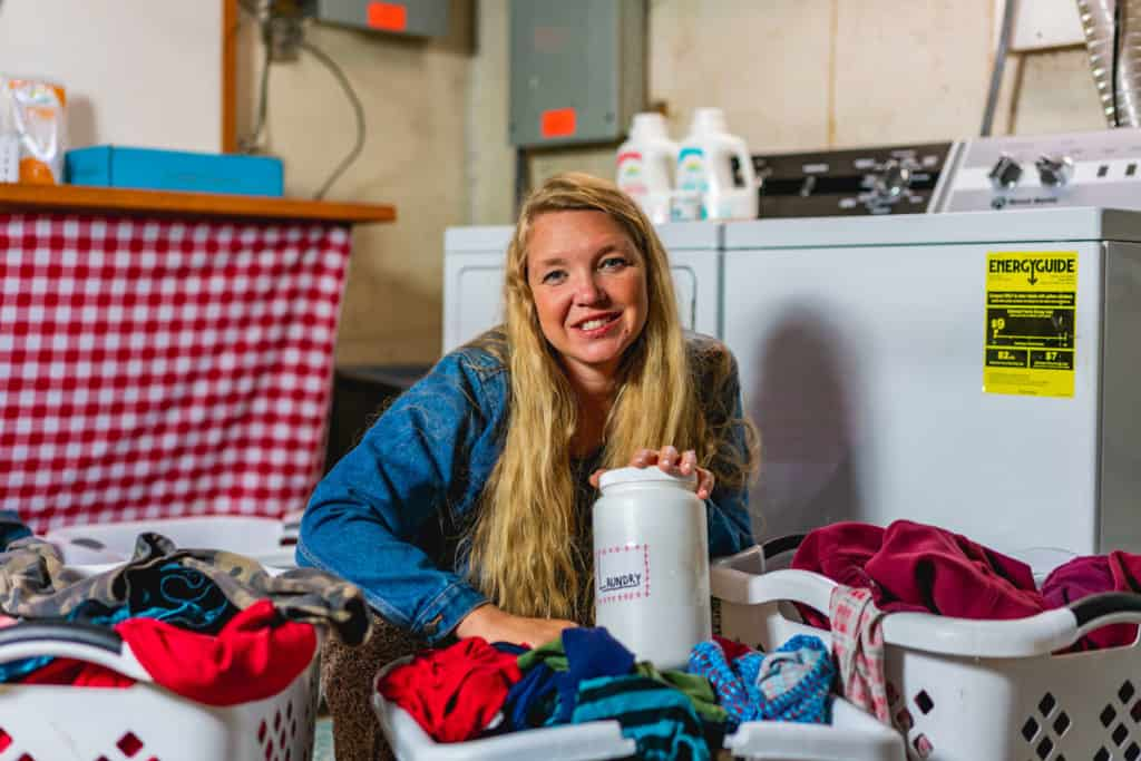 A woman sitting beside baskets of laundry in the laundry room, holding laundry detergent.