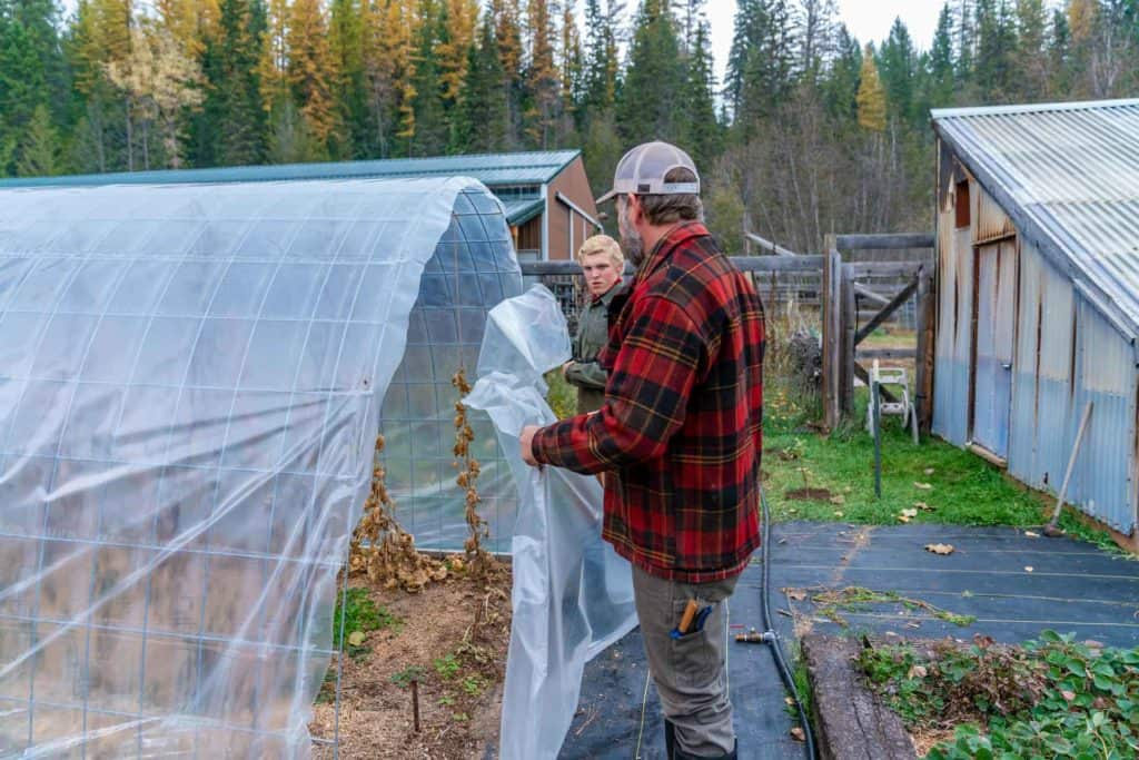 A man removing the plastic covering from a hoop house.