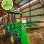 A picture of a tractor scooping hay in a barn for a Pinterest pin on stocking your barn for winter.
