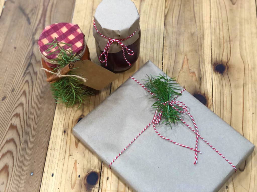 Homemade Christmas gifts wrapped in parchment paper and cut fabric with string and pine branch clippings.