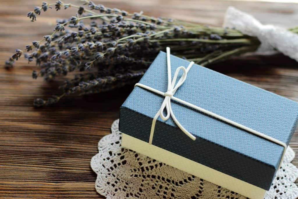 A gift box tied with twine and dried lavender next to it sitting on a table.