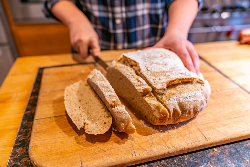 Woman's hands slicing a boule of whole wheat sourdough bread.