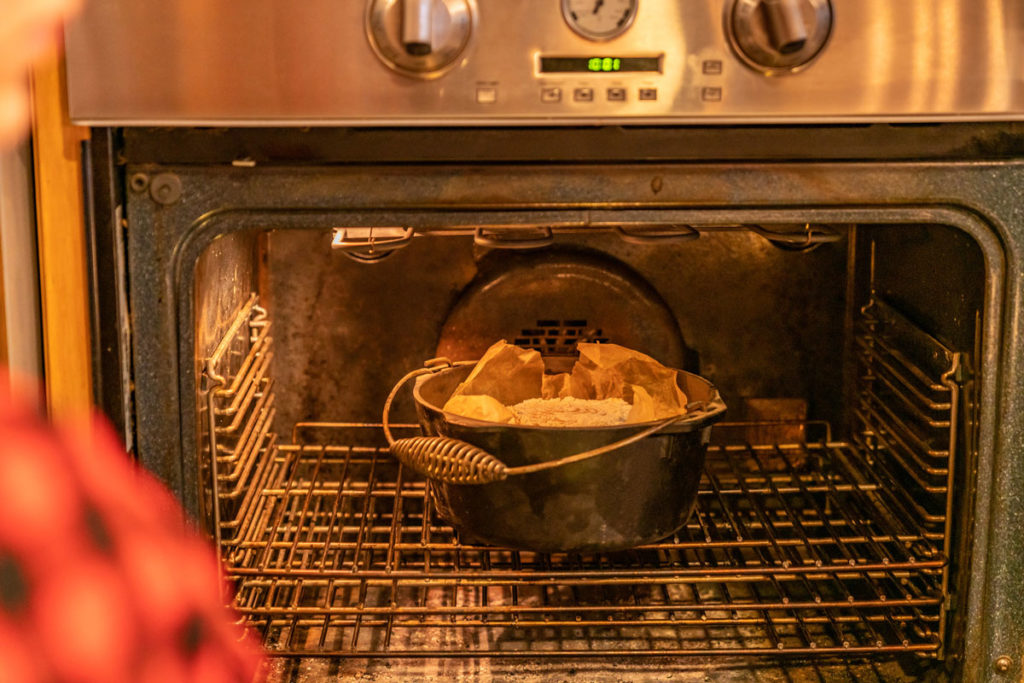 Cast iron dutch oven in the oven with a loaf of artisan bread inside.