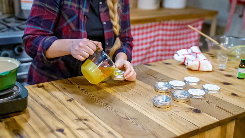 A woman pouring arnica salve into tins.