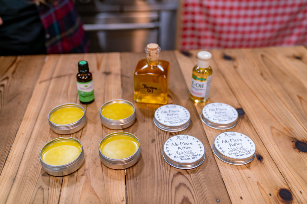 Tins of arnica salve with the ingredients laid out on a table.