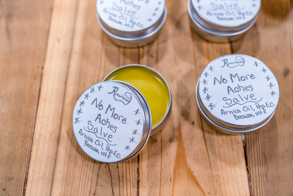 Four tins of homemade arnica oil salve with homemade labels on each tin.